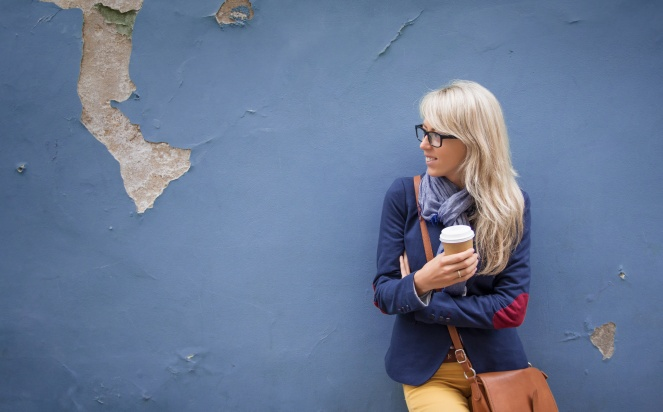 Trendy young woman with cup of coffee standing at the wall